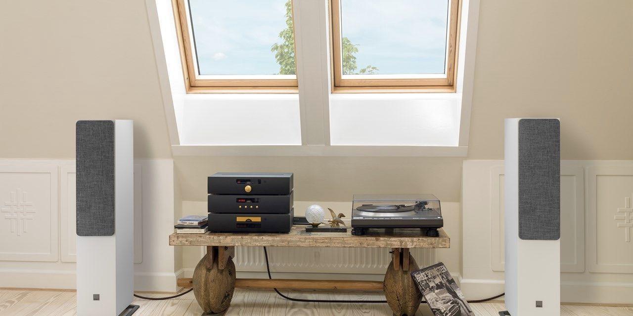 Dali Oberon 7 color blanco con rejilla junto a equipo estéreo